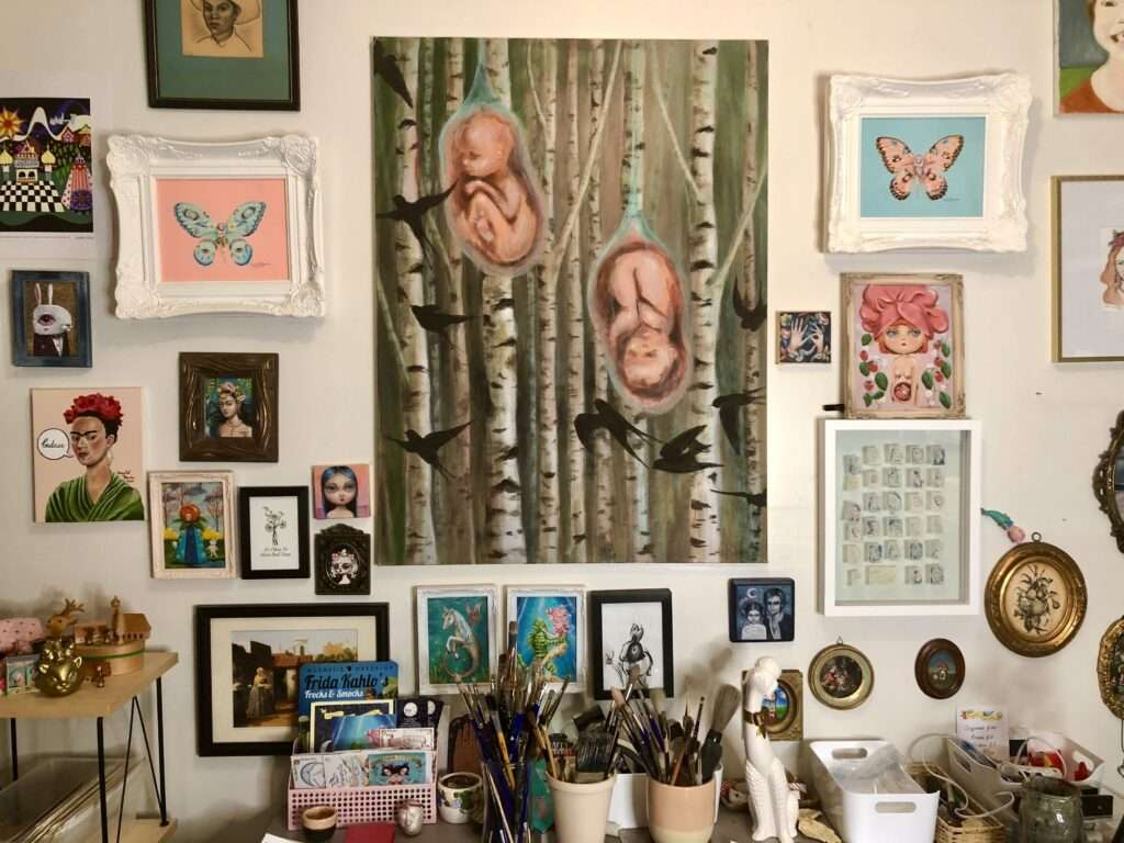 In the center of Marybel Martin's home studio hangs a painting she created early in her pursuit of becoming an artist. The painting shows a grove of birch trees. Among the trees are two babies in the womb surrounded b black birds. The babies represent her sons.